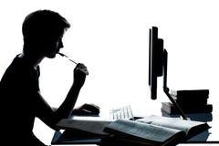 学习与计算机c的一个年轻少年男孩女孩剪影 免版税库存图片