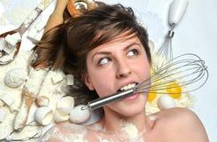 用不同的厨房工具的愉快的相当少妇厨师为c 免版税库存照片