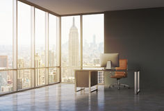 一个工作场所在一个现代壁角全景办公室有日落纽约视图 有现代计算机和棕色皮革的c一张黑书桌 库存照片