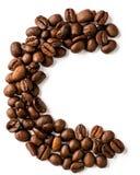 C-bokstav som göras från isolerade kaffebönor på vit bakgrund arkivfoto