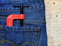 C-clamp. And Jeans on wooden background Stock Photography