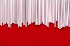 C?ctel colorido de la paja en un fondo rojo foto de archivo
