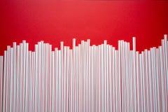 C?ctel colorido de la paja en un fondo rojo imagenes de archivo
