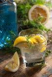 C?ctel con ginebra, t?nico y el lim?n azules en una tabla de madera vieja fotos de archivo libres de regalías