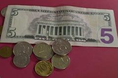 C?dulas e moedas no fundo vermelho fotografia de stock royalty free