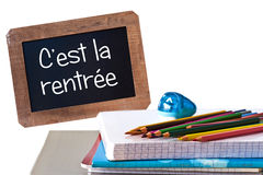C'est la rentree (meaning Back to school) written on black chalkboard. With school supplies Stock Photography