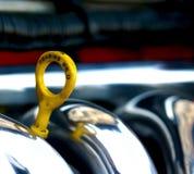 C'est le cou où de l'huile de voiture est versée, de lui colle une poignée jaune qui montre le niveau de l'huile dans le moteur D images libres de droits