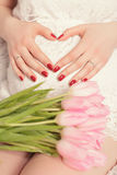 C female hands forming heart shape on belly. pregnant with bouqu. Female hands forming heart shape on belly. pregnant with bouquet of flowers tulips royalty free stock images