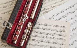 C flute over music scores Stock Photo