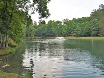 C. G. Hill Memorial Park Fountain. A fountain flows in the middle of the lake at C. G. Hill Memorial Park in Pfafftown, North Carolina Stock Photos