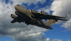 C-17 Globemaster. US military cargo plane flying with a partly cloudy sky Royalty Free Stock Images