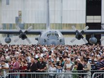 C-130 Hercules aircraft behind crowd of people watching airshow royalty free stock photos