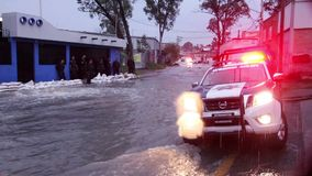 Policemen gard an area affected by the flood, the water flows on the sewers.