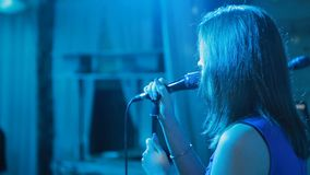 Young singer with a microphone. C lose up portrait of attractive young singer with a microphone stock video