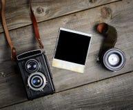 C?mara del vintage con las lentes y la fotograf?a vieja en blanco en fondo de madera imagenes de archivo