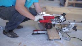 C?mara lenta de la belleza carpintería en la casa - un varón profesional joven monta un piso de madera de pino almacen de metraje de vídeo