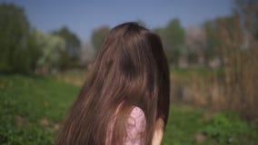 C?MARA LENTA 120fps: Muchacha cabelluda de la mujer del marr?n feliz joven del viajero que sonr?e y que da vuelta alrededor en un almacen de video
