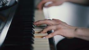 C?mara lenta - los fingeres de la muchacha que juega las llaves del piano almacen de video
