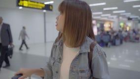 C?mara lenta - mujer asi?tica feliz que usa la carretilla o el carro con mucha el equipaje que camina en pasillo terminal almacen de metraje de vídeo