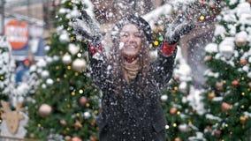 C?MARA LENTA: Nieve que sopla de la mujer joven Nieve que sopla de la mujer joven Retrato de la mujer joven linda que sopla en ni metrajes