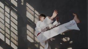 C?mara lenta Un atleta joven en condiciones físicas excelentes muestra retrocesos Él aumenta sus piernas arriba Marcial tradicion almacen de metraje de vídeo