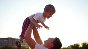 C?mara lenta un padre joven que lanza a su beb? de risa para arriba en el aire Reconstrucci?n al aire libre metrajes