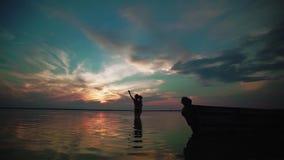 C?mara lenta Una mujer con un ni?o en sus brazos se coloca en el lago y alegre aclara sus manos en un lago en la puesta del sol almacen de metraje de vídeo