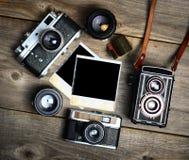 C?maras del vintage con las lentes y la fotograf?a vieja en blanco en fondo de madera imagen de archivo