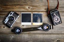 C?maras del vintage con las lentes y la fotograf?a vieja en blanco en fondo de madera imágenes de archivo libres de regalías