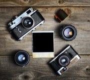 C?maras del vintage con las lentes y la fotograf?a vieja en blanco en fondo de madera imagenes de archivo