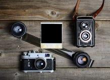 C?maras del vintage con las lentes y la fotograf?a vieja en blanco en fondo de madera fotos de archivo