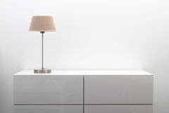 Cômoda branca com o candeeiro de mesa no interior brilhante do minimalismo Fotos de Stock Royalty Free