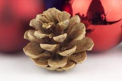 Cône de pin, globes rouges et ornement de Noël Photo libre de droits