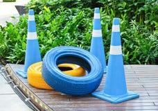 Cônes bleus avec peint pneus bleus et jaunes Image libre de droits