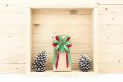 Cônes de boîte-cadeau et de pin de la vie de Stil avec la neige dans la boîte carrée Photographie stock libre de droits