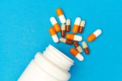 c?psulas & x28; pills& x29; foram derramados de uma garrafa branca em um fundo azul Fundo m?dico, molde fotografia de stock royalty free