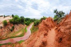 C?rrego que corre abaixo de uma garganta vermelha com o trevo verde na costa em Vietname perto de Mui Ne imagens de stock