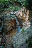 C?rrego, transformando na mini cachoeira Água da cachoeira para afiar a pedra grande fotografia de stock