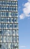 Côté d'un gratte-ciel en verre vertical de bureau avec le ciel bleu vide Image stock