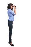 Côté d'une femme occasionnelle regardant par des jumelles Images stock