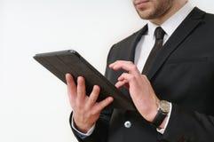 Côté de corps d'homme d'affaires dans le costume noir tenant son comprimé sur le blanc photos stock