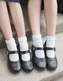 Côté des jambes et des pieds thaïlandais asiatiques d'étudiante d'écolière de filles avec les chaussures noires Photo stock