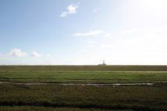 Côte de la Mer du Nord d'Allemand avec le phare sur l'horizon éloigné Photos stock