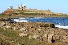 Côte du Northumberland avec le château de Dunstanburgh à l'arrière-plan Photographie stock libre de droits