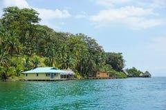 Côte tropicale avec des maisons et des huttes au-dessus de l'eau Images libres de droits