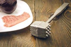 Côtelette crue et marteau d'un plat blanc Photo stock