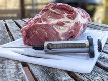 Côtelette de porc injectant avec la seringue de nourriture Images libres de droits