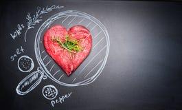 Côtelette en forme de coeur de viande sur le tableau noir avec la casserole et les ingrédients peints, vue supérieure, endroit po Photo stock