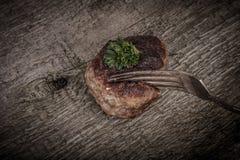 Côtelette et tranche sur une fourchette sur la vieille table en bois Images stock