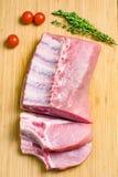 Côtelette, tomates et thym de porc sur le fond en bois image stock
